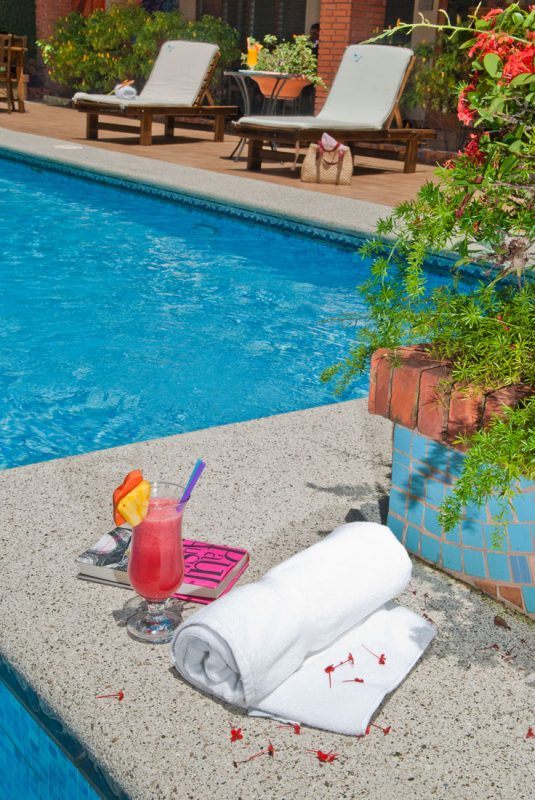 Enjoy a drink at the pool at Hotel y apartaments La Sabana